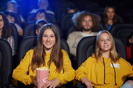 Front view of two young girls wearing same yellow sweaters watching movie in cinema and laughing. Cheerful caucasian female teenagers enjoying film with friends. Entertainment concept.