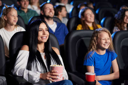 Side view of stunning brunette girl holding popcorn, watching comedy with younger sister in cinema, laughing with teeth. Cheerful caucasian female teenager wearing shirt, enjoying film with family. Reklamní fotografie