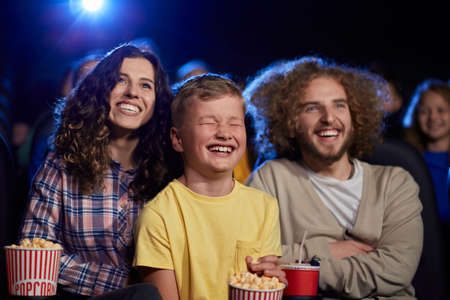 Selective focus of parents with curly hair enjoying time with son holding sparkling drink in cinema. Happy young family sitting in cinema, kid laughing with closed eyes, watching funny cartoon.