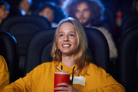 Selective focus of young blonde girl watching movie in cinema, holding sparkling drink and laughing. Cheerful caucasian female teenager wearing yellow sweater enjoying film. Entertainment concept.