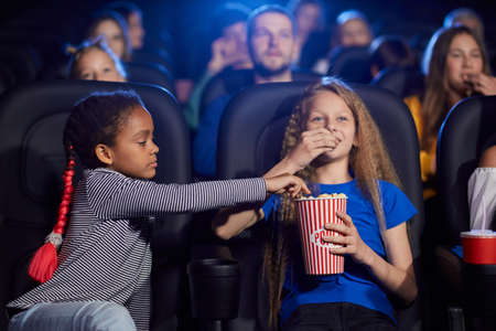 Kids enjoying time together, young multiracial audience on background. Happy friends sitting in cinema, watching funny cartoon, caucasian girl eating and sharing popcorn with african female friend.