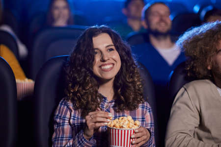 Selective focus of young girl with brown curly hair watching movie in cinema, eating popcorn and laughing. Cheerful attractive caucasian girl enjoying film with friends. Entertainment concept. Reklamní fotografie
