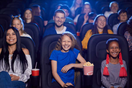 Cheerful kids enjoying time together holding sparkling drink, young multiracial audience on background. Happy little friends sitting in cinema, watching funny cartoon. Entertainment concept. Reklamní fotografie