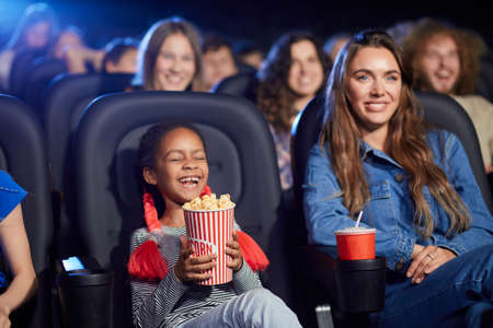 Front view of little african female kid laughing in cinema seat, holding popcorn. Young attractive caucasian woman spending time in movie theater with child, watching funny cartoon.