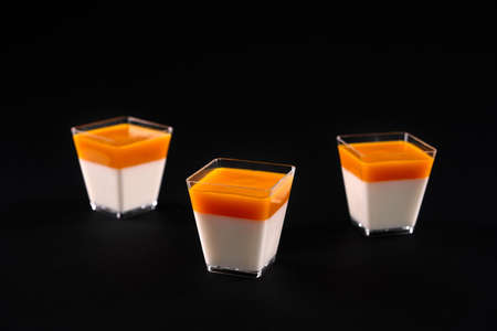 Front view of three small square glasses with milky panna cotta decorated with bright orange topping. Sweet delicious dessert isolated on black studio background. Food concept. 版權商用圖片