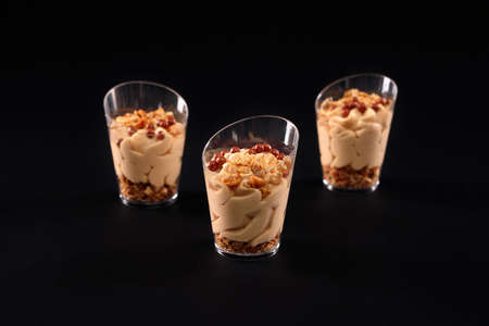 Closeup view of fresh homemade sweet creamy granola dessert in three small glasses in row isolated on black background. Tasty parfait decorated with brown balls on top and chocolate whipped cream.