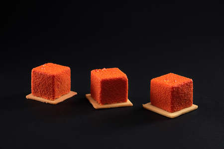 Three small orange square matte cakes in row on cookies in restaurant. Concept of confectionary. Closeup view of matte fresh dessert isolated on black studio background.
