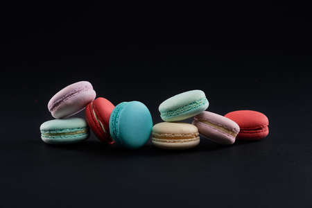 Front closeup view of colorful assorted macaroons with differest tastes. Delicious sweet dessert cookies on table, isolated on black background. Concept of sweet pastry.