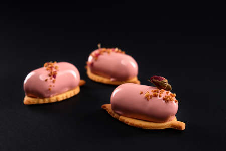 Pink cakes decorated with dry rose flower and nuts. Dessert with smooth surface, mousse and mirror glaze on cookie isolated on black studio background. Tasty sweet dish in cafeteria. Reklamní fotografie