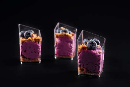 Front view of delicious sweet muesli dessert in three small glasses in row. Tasty parfait with granola, blueberries on top and bright purple whipped cream isolated on black background. Reklamní fotografie