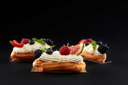 Baked homemade eclairs filled with cream, white topping and slices of figs, blackberries, raspberries and blueberries. Side view of fresh dessert in row isolated on black background.