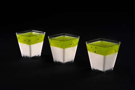 Front view of three small square glasses with milky panna cotta. Sweet delicious dessert decorated with bright green apple topping, isolated on black background. Food concept. Reklamní fotografie