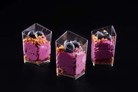 Front view of delicious sweet dessert in three small glasses in row isolated on black background. Tasty parfait with granola, blueberries on top and bright purple whipped cream. Reklamní fotografie