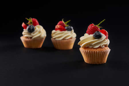 Three fresh tasty cupcakes in row isolated on black background. Closeup front view of sweet delicious dessert with white creamy topping, strawberry, blueberyy and rasberry slices. Reklamní fotografie
