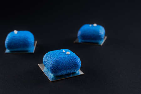 Three small matte cakes in row in restaurant isolated on black studio background. Closeup view of matte blue dessert decorated with white balls. Concept of confectionary, bakery.
