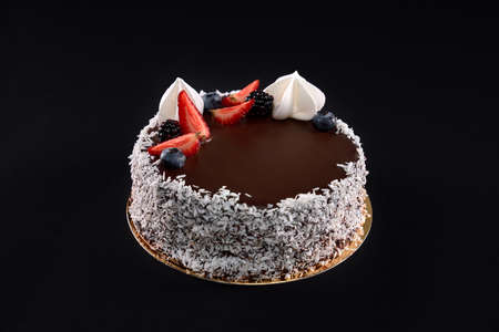 Top view of beautiful tasty brown cake decorated with coconut shaving on sides, fresh berries and white cream. Delicious dessert with chocolate topping isolated on black background.