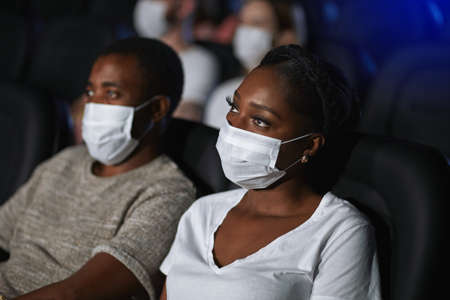 Side view of african man and woman enjoying film during world pandemic. Selective focus of young couple watching movie in cinema, sitting in comfortable black seats, wearing white face masks. 版權商用圖片