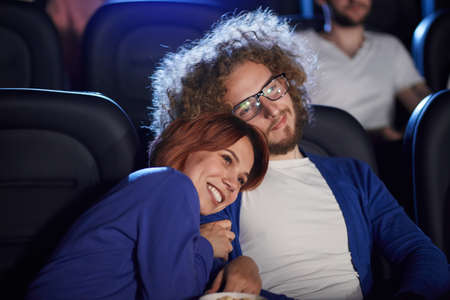 Front view of young lovely couple watching movie in cinema. Selective focus of caucasian girl smiliing with teeth lying on shoulder of bearded boyfriend with afro hairstyle. Concept of entertainment.