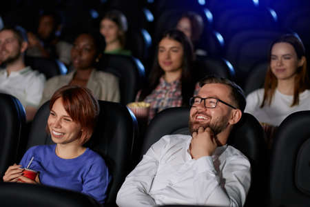 Caucasian couple watching funny comedy in cinema. Selective focus of attractive red heaeded girl and handsome bearded boyfriend in eyeglasses smiling with teeth. Entertainment concept. 版權商用圖片