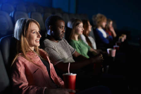Selective focus of young smiling girl watching movie in cinema and holding fizzy sparkling drink. Side view of caucasian girl enjoying film with multiracial friends. Entertainment concept. 版權商用圖片