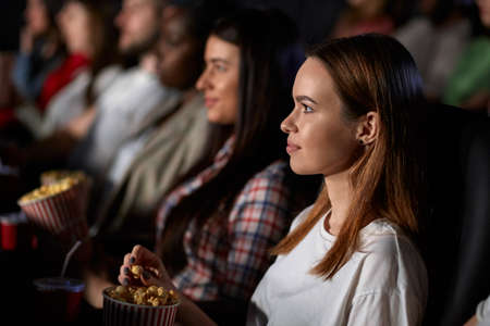 Selective focus of young female friends watching movie in cinema, sitting in comfortable seats. Side view of smiling caucasian girl enjoying film with multiracial audience. Entertainment concept. 版權商用圖片