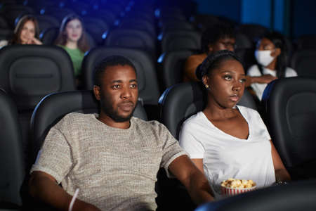 Selective focus of young african couple watching movie in cinema, sitting in comfortable black seats, wearing casual t shirts. Side view of man and woman with strong faces enjoying film.