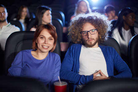 Portrait of young caucasian couple enjoying film in movie theater, posing together. Selective focus of beautiful red headed woman and boyfriend with afro hairstyle looking at camera and smiling.
