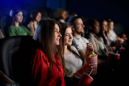 Selective focus of young female teen friends watching movie in cinema, sitting in comfortable seats. Side view of smiling caucasian girl enjoying film with group of people. Entertainment concept.