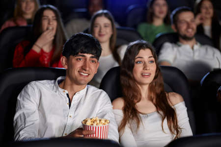 Selective focus of young man laughing, holding popcorn while watching comedy in cinema. Front view of caucasian man and pretty woman enjoying funny film. Concept of entertainment. 版權商用圖片