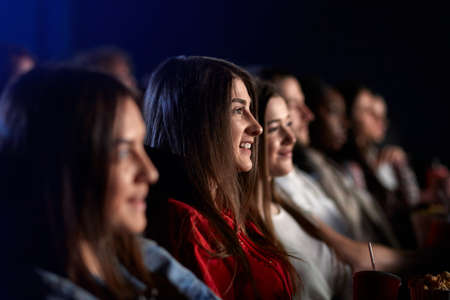 Side view of young stunning brunette girl watching movie in cinema, wearing casual outfit. Selective focus of caucasian girl smiling with teeth enjoying film with friends. Entertainment concept. 版權商用圖片