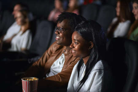 Side view of young african couple enjoying film in movie theater, posing together. Selective focus of beautiful brunette woman with boyfriend smiling and looking at screen. Concept of entertainment. 版權商用圖片