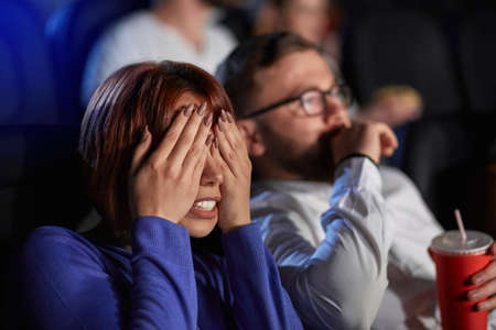 Selective focus of young scared girl covering eyes with hands, watching horror movie in cinema. Side view of scared bearded caucasian man and red headed woman enjoying frightening film.