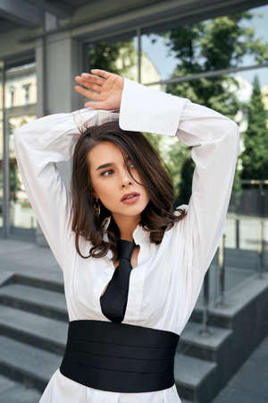Fashionable female model wearing white shirt, black tie and wide corset belt looking aside, strong face and mouth open. Side view of young business woman posing with hands up near office building. 版權商用圖片