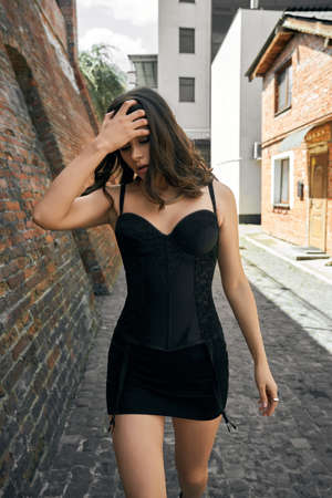 Front view of young pretty caucasian woman with dark brown hair wearing black dress with sexy lace corset and suspenders walking outdoors. Portrait of female model touching hair near brick walls.