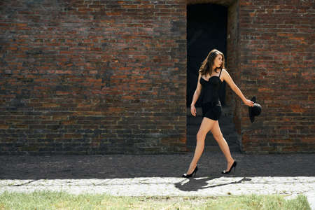 Side view in motion of brunette caucasian female model wearing sexy short black dress and high heels carrying wide hat. Young gorgeous woman walking outdoors, big old brick wall on background.