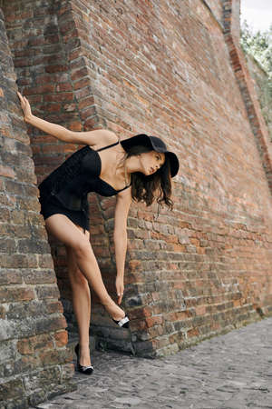 Side full length portrait of young brunette caucasian woman wearing total black look and hat touching high heel shoes. Elegant sexy female model bending, leaning on huge old brick wall.