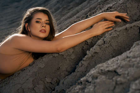 Closeup portrait of astonishing caucasian female model wearing beige outfit posing in dry empty quarry in hot summer sunny day. Young stylish woman lying on black sand outdoors, looking at camera. 版權商用圖片