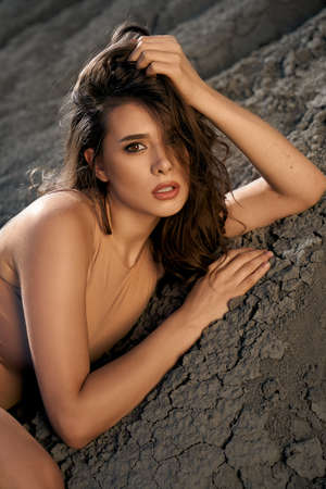 Closeup portrait of astonishing caucasian female model wearing beige outfit posing in dry empty quarry in hot summer sunny day. Young stylish woman lying on black sand outdoors, touching hair.
