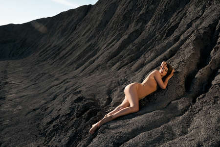 Side view of sensual caucasian female model wearing beige body posing in dry empty quarry in hot summer sunny day. Young stylish barefoot woman lying on black cracked ground and looking at camera.
