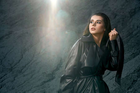 Front view of stunning caucasian female model wearing black leather trench coat on naked body posing in dry empty quarry. Young fashionable woman looking aside, holding belt, black sand outdoors.