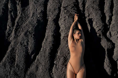 Top view of astonishing beautiful caucasian female model wearing beige body posing in dry empty quarry. Young fashionable woman lying on black sand outdoors in hot summer sunny day..