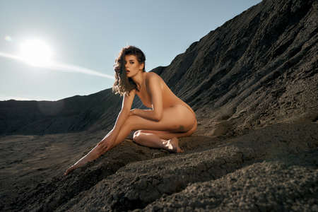 Side view of pretty female model wearing beige body posing in dry empty quarry in hot summer sunny day. Young stylish caucasian woman siitting on black sand outdoors and looking at camera. 版權商用圖片