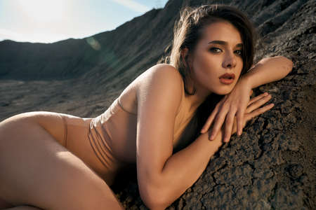 Side view of stunning female model wearing beige body posing in dry empty quarry in hot summer sunny day. Young caucasian woman with mouth open lying in sleeping pose on black cracked ground outdoors.