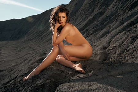 Side view of gorgeous female model wearing beige body posing in dry empty quarry in hot summer sunny day. Young caucasian barefoot fashionable woman sitting on black sand outdoors.