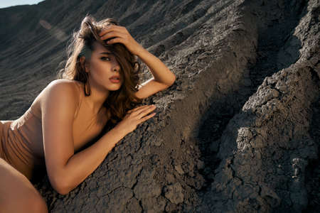Young woman lying in sleeping pose on black cracked ground, touching hair and looking at camera. Stunning female model wearing beige body posing in dry empty quarry in hot summer sunny day.