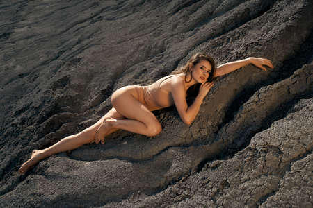 Top view of stunning caucasian female model wearing beige body posing in dry empty quarry in hot summer sunny day. Young woman lying in sleeping pose on black cracked ground, looking at camera. 版權商用圖片
