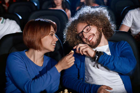 Happy caucasian couple enjoying comedy in movie theater together and smiling. Young emotional caucasian woman watching film giving popcorn to boyfriend with afro hairstyle in cinema.