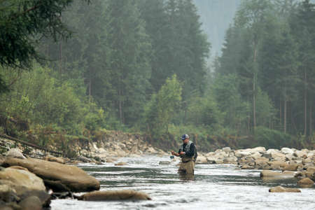 Professional fisherman standing in water with fishing rod and trying to catch fish. Amazing natural landscape on background. Mountain river.