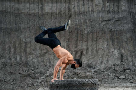 Strong male athlete with naked torso doing active workout on large black wheel. Handsome man wearing face mask during outdoors sport activity.