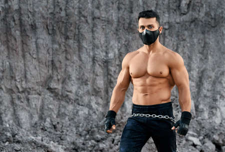 Front view of strong man with naked torso in black protective mask posing among sand quarry. Active guy enjoying sport activity on fresh air.